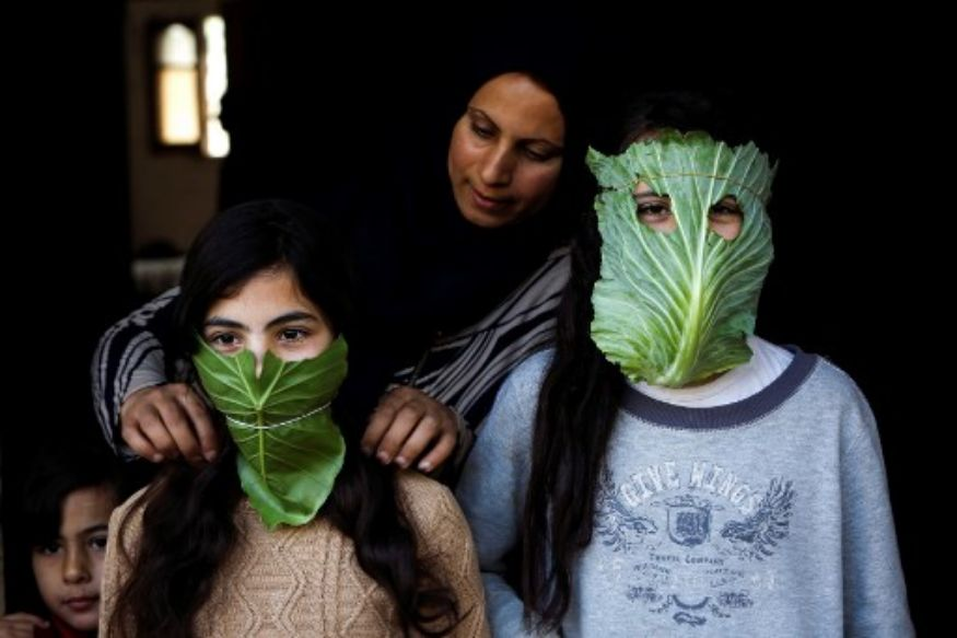 two people wearing cabbage leaves as face masks