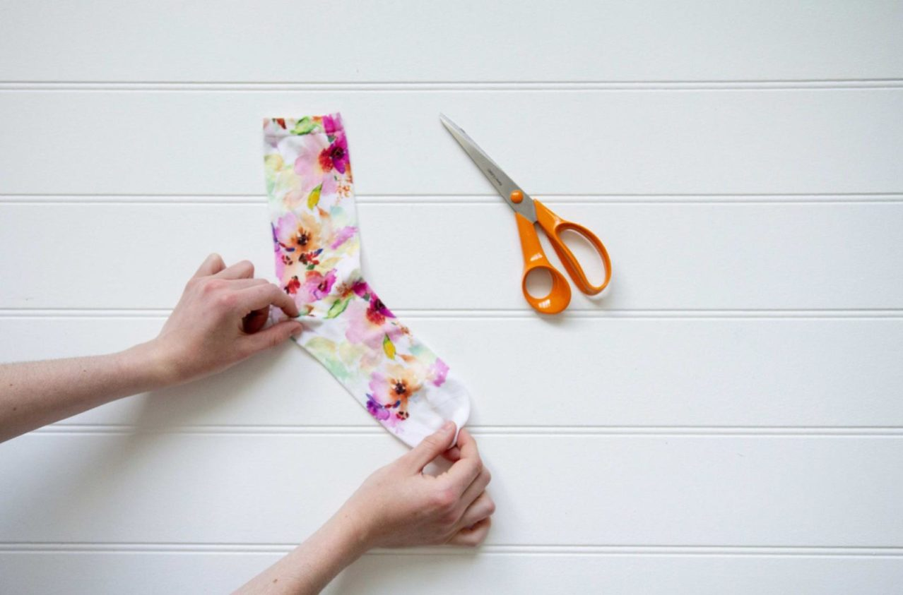 hands holding a floral sock next to scissors